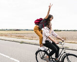 Happy young couple riding together on one bicycle on country road - UUF15448