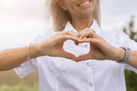 Mature woman shaping heart with her hands - JUNF01440
