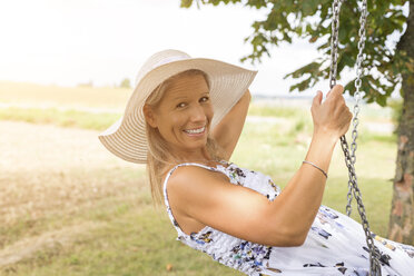 Happy mature woman on swing in remote countryside - JUNF01443