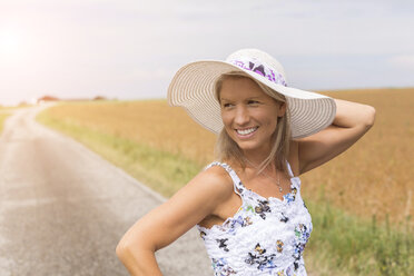 Smiling mature woman on remote country lane in summer - JUNF01449