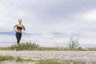 Mature woman running on remote country lane in summer - JUNF01455