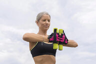 Mature woman doing workout with dumbbells outdoors - JUNF01461