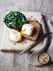 Still life with spinach and poached egg on toast on chopping board, overhead view - CUF44629