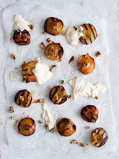 Roasted peaches on baking sheet with cream - CUF44794