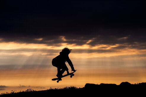 Young boy skateboarding at sunset, jumping, in mid air, Doolin, Clare, Ireland - CUF44887