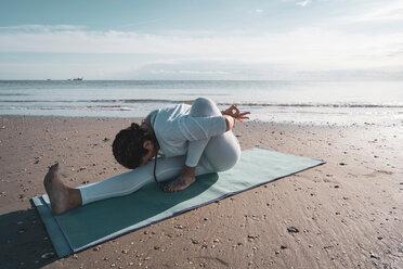 Woman practising yoga on beach - CUF44989