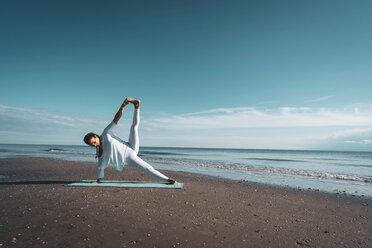 Woman practising yoga on beach - CUF44992
