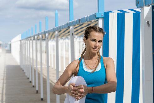 Woman practising yoga by beach - CUF44998
