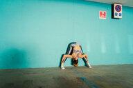 Woman practising yoga in parking lot - CUF45007