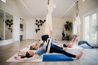Women doing aerial yoga at retreat - CUF45010