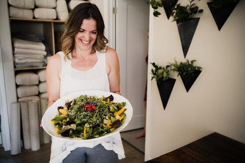 Woman serving large dish of salad at retreat - CUF45022