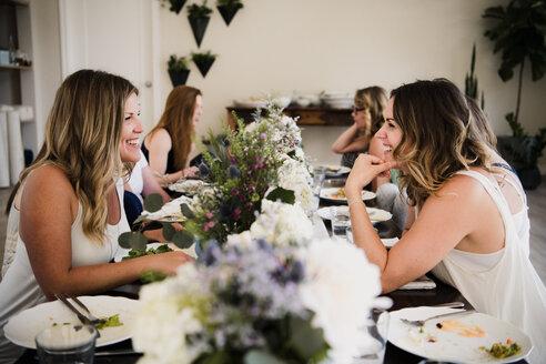 Women enjoying friendship and meal in yoga retreat - CUF45028