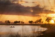 Tourists on canoe safari at sunset on lower Zambezi River in Zambia - LUXF00854