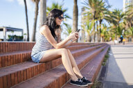 Spain, Barcelona, smiling young woman sitting on steps at sunlight using cell phone - GIOF04609