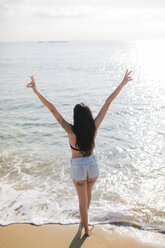 Back view of young woman standing at seashore showing victory sign - GIOF04630