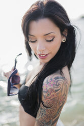 Portrait of smiling young woman with nose piercing and tattoo on her shoulder at the sea - GIOF04633