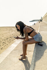 Smiling young woman with nose piercing and tattoos using smartphone near the beach - GIOF04636