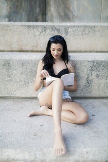 Portrait of tattooed young woman with black hair reading a book - GIOF04642