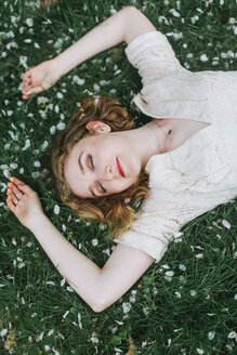 Woman lying down on blossom covered grass, overhead view - CUF45107