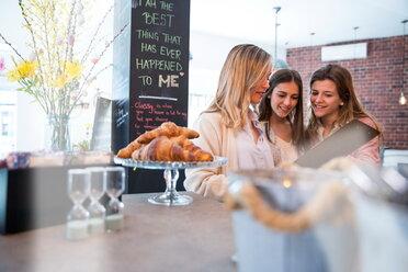 Three female friends, looking at menu in cafe - CUF45113