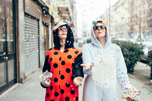 Women wearing adult bodysuits throwing confetti in street - CUF45137