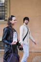 Portrait of happy young man walking hand in hand with his girlfriend - GIOF04664