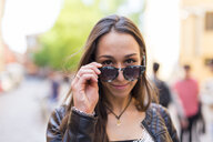 Portrait of smiling young woman with sunglasses - GIOF04673