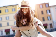Portrait of happy young man giving his girlfriend a piggyback ride - GIOF04679