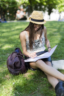 Smiling young student sitting on a meadow in a park using copybook - GIOF04682