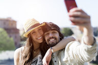 Portrait of happy young couple taking selfie with smartphone - GIOF04694