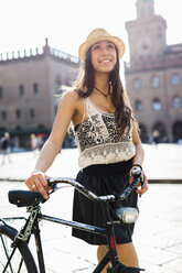 Italy, Bologna, portrait of fashionable young woman with bicycle in the city - GIOF04706