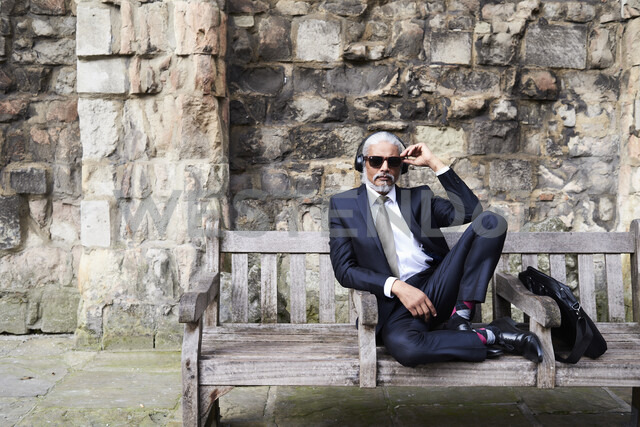 Portrait of well-dressed senior businessman with sunglasses and headphones sitting on bench - IGGF00614