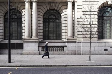 UK, London, senior businessman walking on pavement in the city - IGGF00617