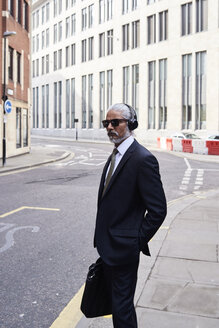 Portrait of elegant senior businessman with sunglasses and headphones standing on sidewalk - IGGF00620