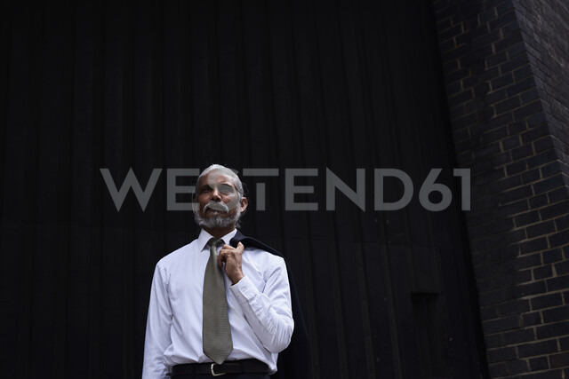 Portrait of senior businessman with grey hair wearing white shirt and tie standing against dark background - IGGF00626
