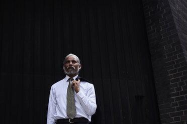 Portrait of senior businessman with grey hair wearing white shirt and tie standing against dark background - IGGF00626
