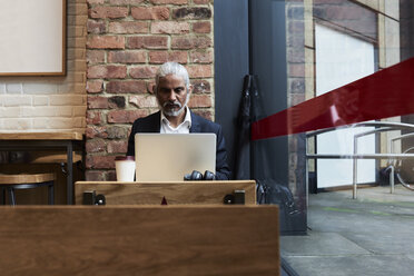 Senior businessman working on laptop in a coffee shop - IGGF00635