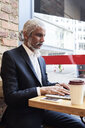 Senior businessman sitting in a coffee shop working on laptop - IGGF00638