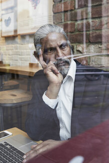 Portrait of pensive senior businessman in a coffee shop looking out of window - IGGF00641