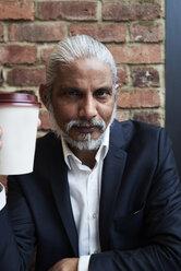 Portrait of bearded senior businessman with coffee to go - IGGF00644