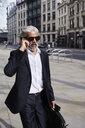 Portrait of smart senior businessman talking on the phone - IGGF00647