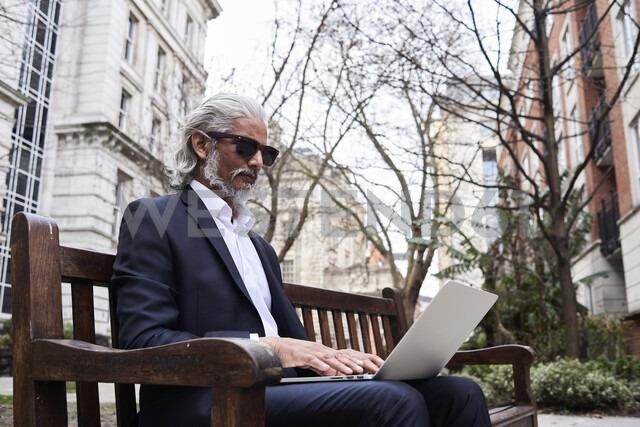 UK, London, senior businessman sitting on bench outdoors working on laptop - IGGF00650