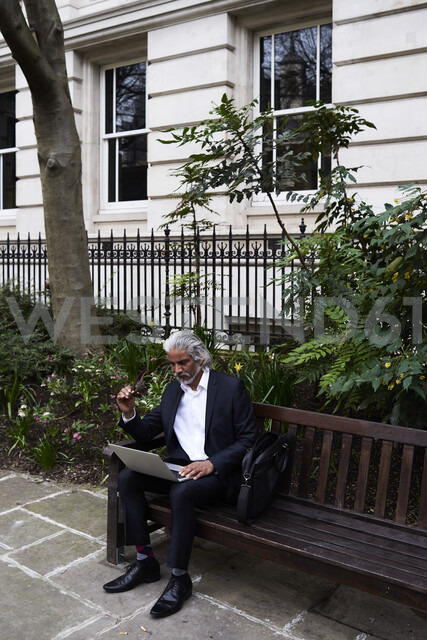 Senior businessman sitting on bench outdoors working on laptop - IGGF00653