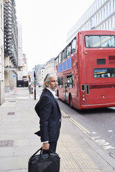 UK, London, senior businessman with luggage waiting at crosswalk - IGGF00656