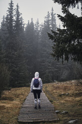 Bulgaria, Young yoman walking through the forest, rainy weather - BZF00465