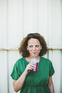 Portrait of smiling woman drinking fruit smoothie outdoors - HMEF00018