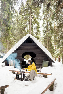 Finland, Kuopio, woman preparing campfire in winter - PSIF00112