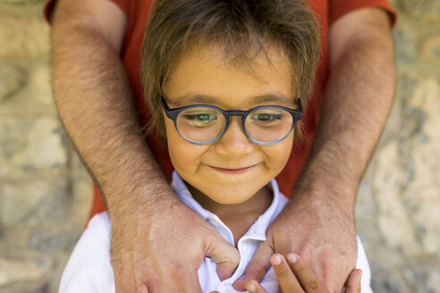 Portrait of smiling little boy wearing glasses standing in front of his father - VABF01622