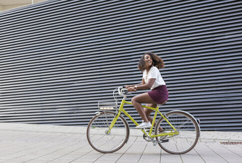 Smiling young woman riding bicycle - JUNF01474