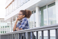 Pensive young woman leaning on railing looking at distance - JUNF01486